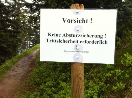 Neu angebrachtes Warnschild auf dem schmalen Bergpfad